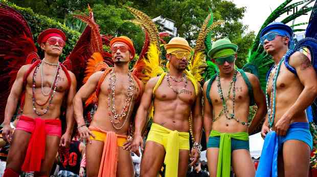 at there Taipei Gay and LGBT Pride Parade five men, each with twink-esque outfit in one color, from right to left: red, orange, yellow, green, and blue. They make most of the LGBT pride flag. They each have on mini-boxers weeks, do-rags, hats, and shades.