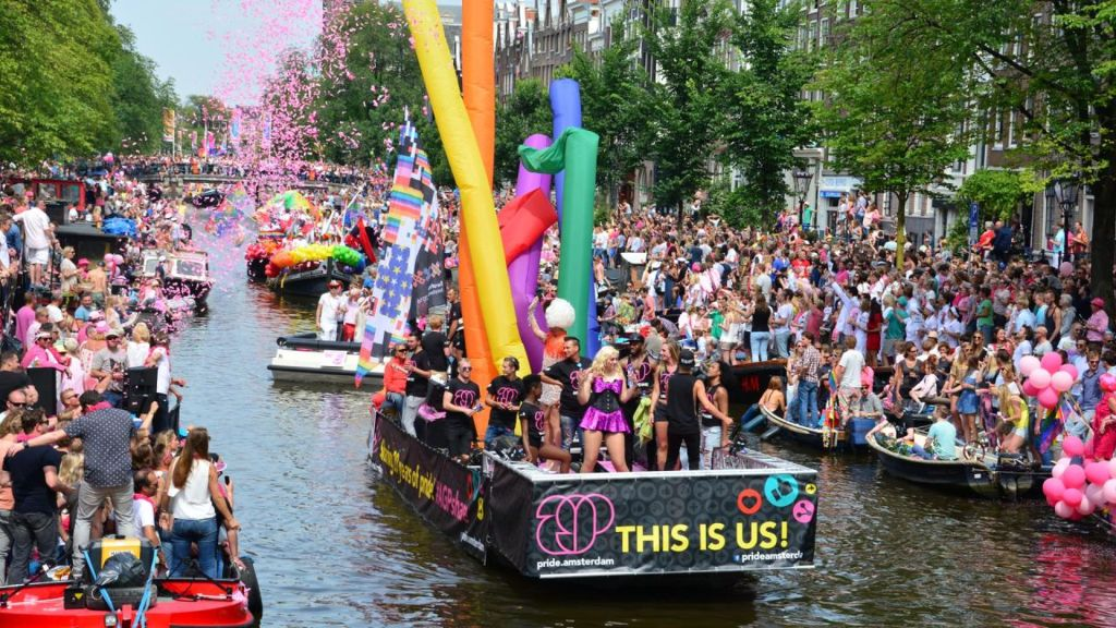 Gay pride parade in Amsterdam. Float with rainbows and confetti floating on a canal.