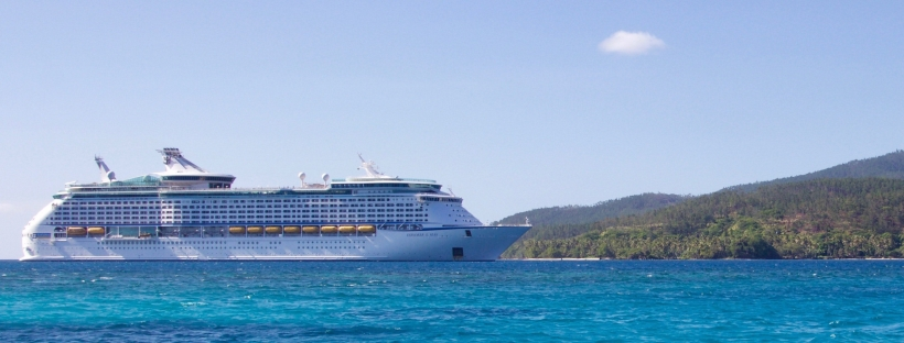 Cruise ship on a repositioning cruise in perfect blue waters under clear blue skies with beach and mountains in the background.